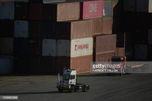 Trucks drive past cargo shipping containers at the Port of Los Angeles on October 15, 2021 in San Pedro, California. - The port, North America's...