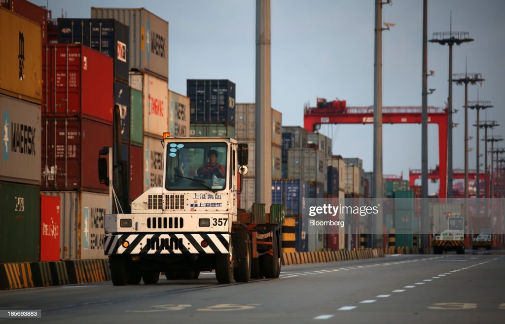 Trucks drive past shipping containers stacked at the Yangshan Deep Water Port, part of China (Shanghai) Pilot Free Trade Zone's Yangshan free trade port area, in Shanghai, China, on Wednesday, Oct. 23, 2013. The area is a testing ground for free-market policies that Premier Li Keqiang has signaled he may later implement more broadly in the world's second-largest economy. Photographer: Tomohiro Ohsumi/Bloomberg via Getty Images