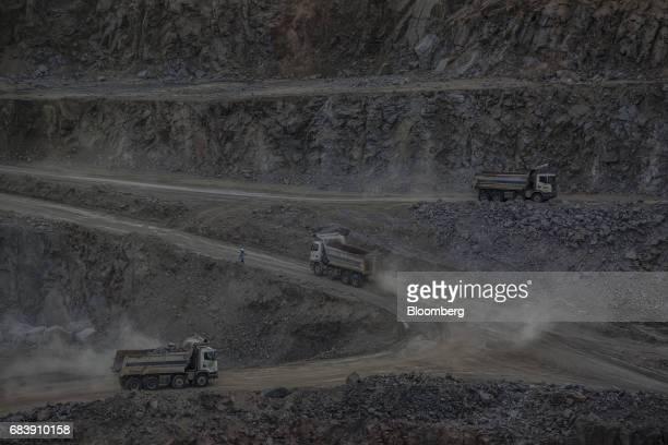Trucks drive through the open pit at the Lipari Mineracao Ltda Brauna Diamond Mine in the Municipality of Nordestina State of Bahia Brazil on...