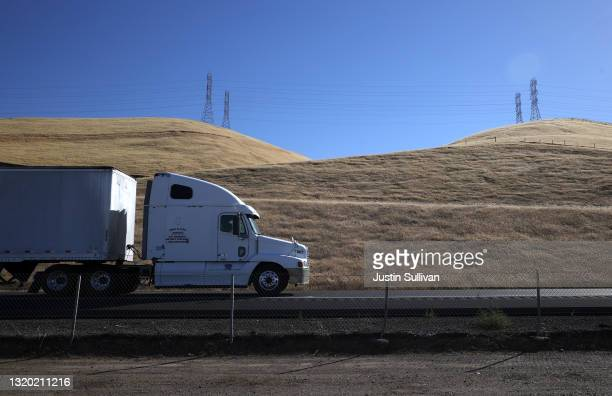 Trucks drives by hills covered in dry grass along Highway 5 on May 25, 2021 in Los Banos, California. As California enters an extreme drought...