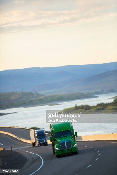 trucks driving on remote highway - ship front view stock photos and pictures