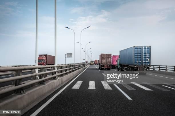 trucks driving on the highway - lkw stock-fotos und bilder