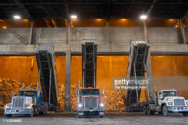 Trucks equipped with special containers that can hold up to 25 tons of garbage dump the contents in the tipping hall of the Covanta Energy Montgomery...