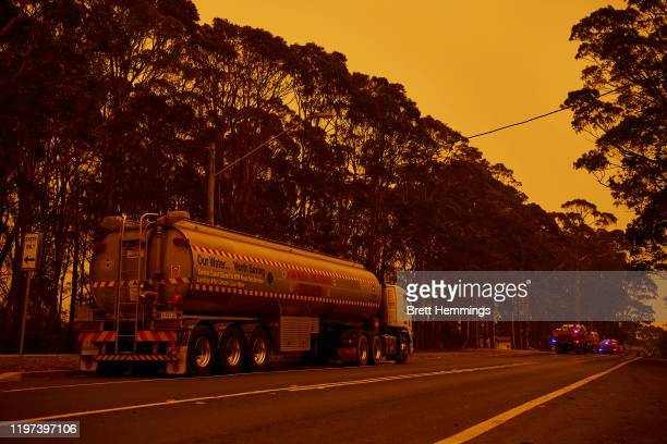 Trucks gather in front of the RFS station on January 04, 2020 in Bodalla, Australia. A state of emergency has been declared across NSW with dangerous...