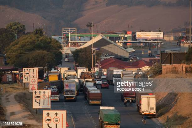 Trucks line up outside the Oshoek border-post on the South African side of the border with Eswatini on July 1, 2021. - Demonstrations escalated...