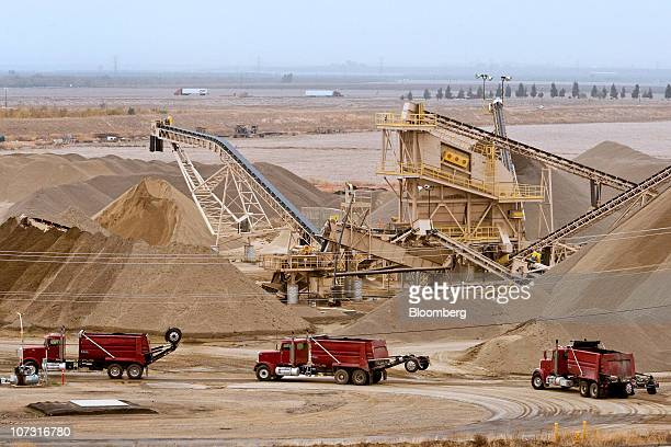 Trucks line up to be loaded with hot mix at Granite Construction Inc's Hot Mix and Aggregate Vernalis plant in Tracy California US on Thursday Dec 2...