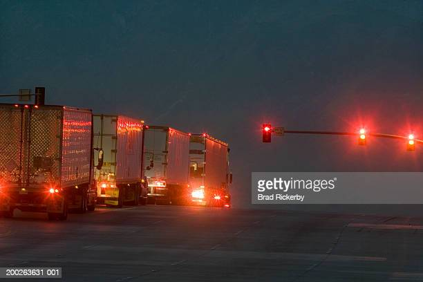 Trucks lined on street waiting to make turn, rear view