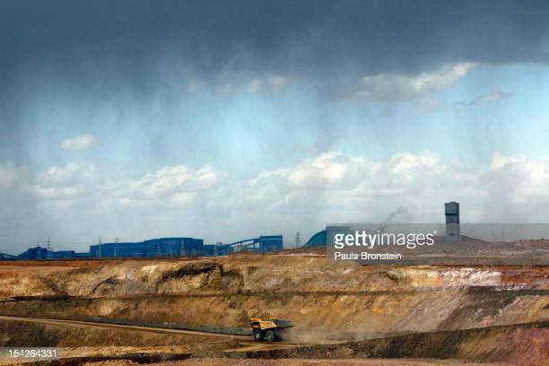 Trucks move tons of ore at the open pit mining area as a rainstorm approaches at the Oyu Tolgoi mine October 11 2012 in the south Gobi desert...