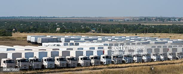 Trucks of Russian humanitarian convoy are parked in a field outside the town of KamenskShakhtinsky in Rostov region some 30 km from the...