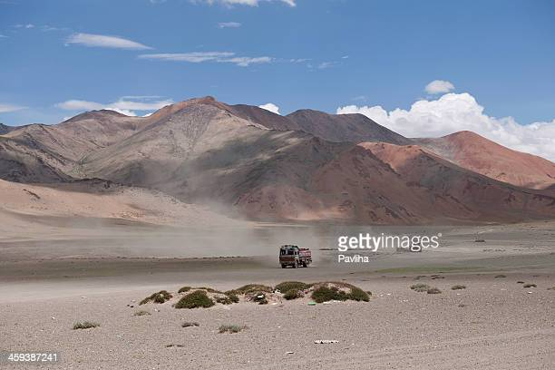 trucks on dry plateau mora india - pavliha stock photos and pictures