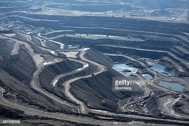 Trucks operate around the open pit of the Neryungrinsky coal mine operated by OAO Mechel in this aerial view in Neryungri Sakha Republic Russia on...