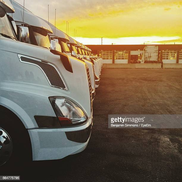 Trucks Parked In Row At Parking Lot Against Orange Sky