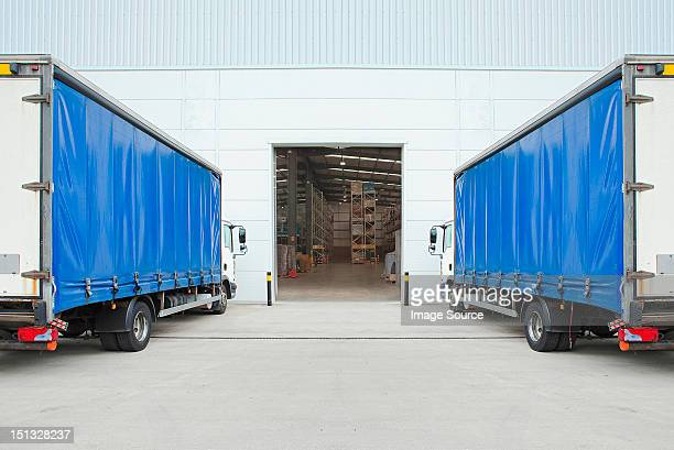 trucks parked outside distribution warehouse - loading dock stock pictures, royalty-free photos & images