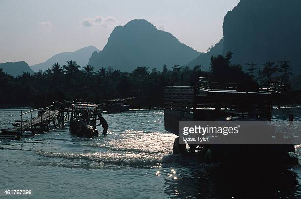 Trucks passing from bank to bank at the main river in Vang Vieng. A spectacular environment with stunning scenery, Vang Veing is home to a series of...