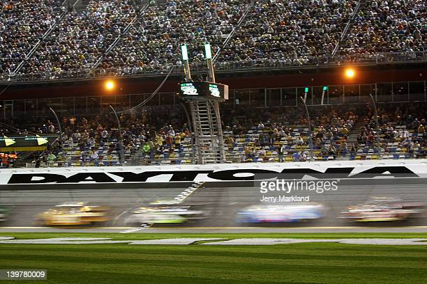 Trucks race down the frontstretch during the NASCAR Camping World Truck Series NextEra Energy Resources 250 at Daytona International Speedway on...