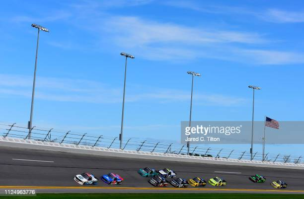 Trucks race in a pack during practice for the NASCAR Gander Outdoor Truck Series NextEra Energy 250 at Daytona International Speedway on February 14...