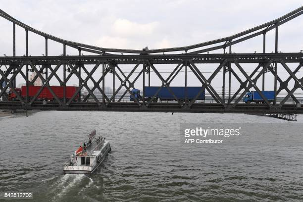 Trucks return over the Friendship Bridge from the North Korean town of Sinuiju to the Chinese border city of Dandong in China's northeast Liaoning...