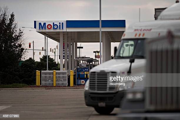 Trucks sit in a parking lot outside a Mobil gas station in Morton Illinois US on Wednesday Oct 29 2014 Exxon Mobil Corp is scheduled to report...