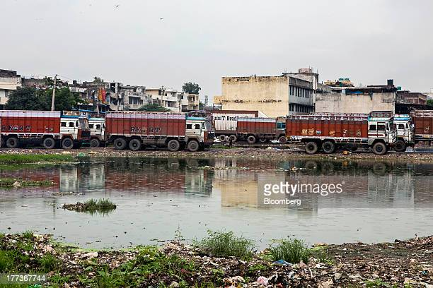 Trucks sit parked between pools of water at the Sanjay Gandhi Transport Naga depot in New Delhi India on Thursday Aug 22 2013 Indias rupee plunged 44...