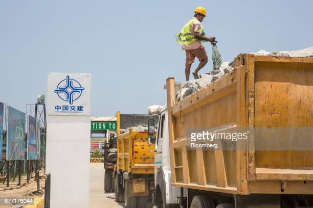 Trucks sit parked next to signage for China Communications Construction Co near an entrance to the Colombo Port City development in Colombo Sri Lanka...