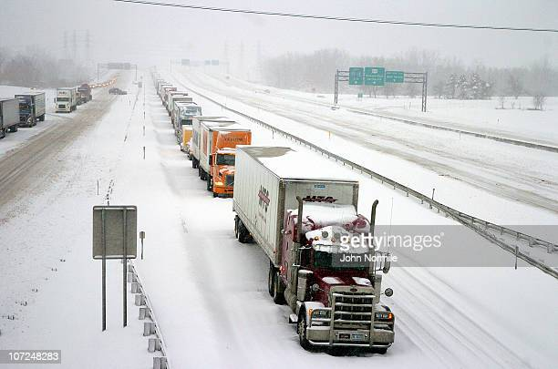 Trucks stand still along the New York State Thruway after a five mile wide band of lake-effect snow dumped more than two feet of snow and closed a...