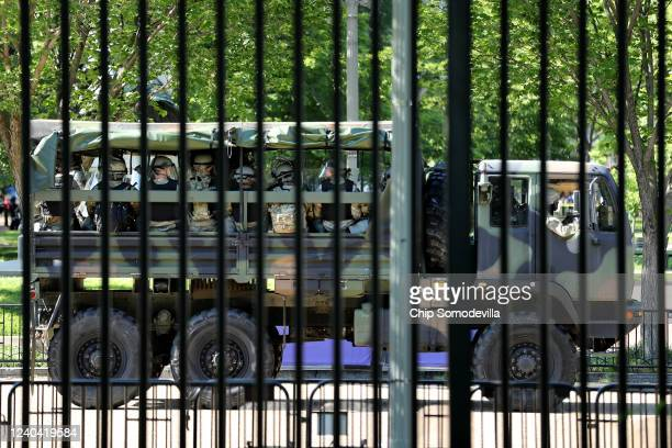 Trucks transport District of Columbia National Guard troops along Pennsylvania Avenue in support of law enforcement officers that are keeping...