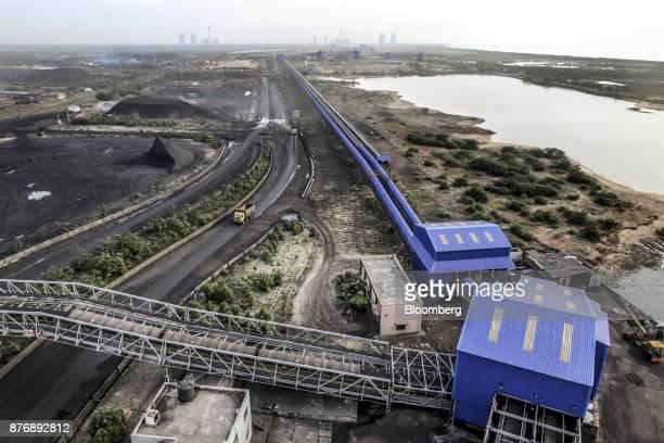Trucks transport materials as a conveyor runs through Krishnapatnam Port in Krishnapatnam Andhra Pradesh India on Saturday Aug 12 2017 Growth in...