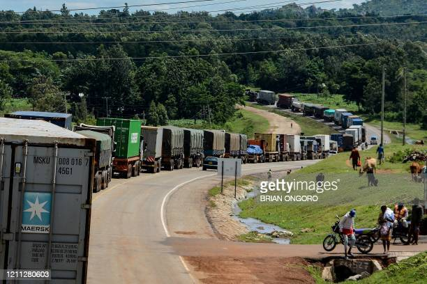 Trucks wait in a line on the road to enter Uganda in Malaba, a city bordering with Uganda, western Kenya, on April 29, 2020. - All truck drivers...