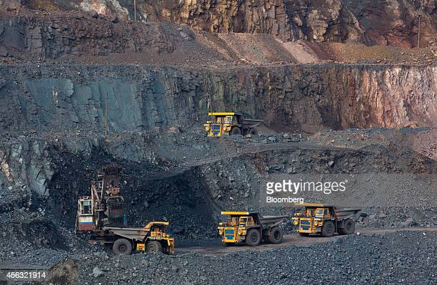 Trucks wait to collect iron ore from an excavator in the open pit of the Stoilensky GOK iron ore mine and processing plant operated by OAO...