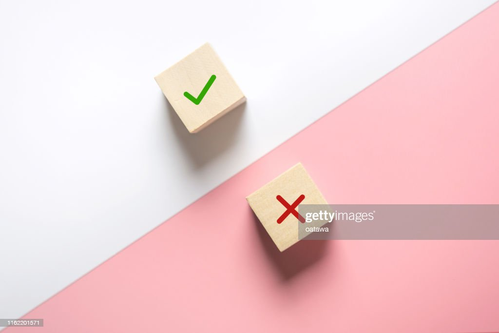 True and false symbols accept rejected for evaluation, Yes or No on wood blogs on pink and white background. : Stock Photo
