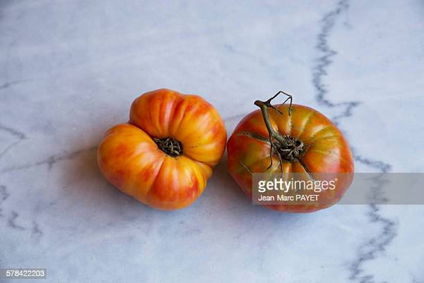 """true organic tomatoes """"beef heart"""" on a marble tab - jean marc payet photos et images de collection"""