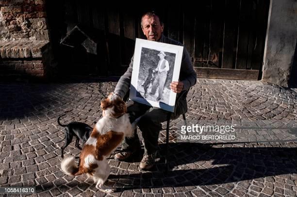 Truffle hunter Giovanni Monchiero poses with a picture of his grandfather Giovanni Monchiero in Roddi near Alba northwestern Italy on October 24 2018...