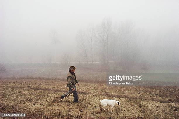 Truffle hunter with dog, walking in countryside