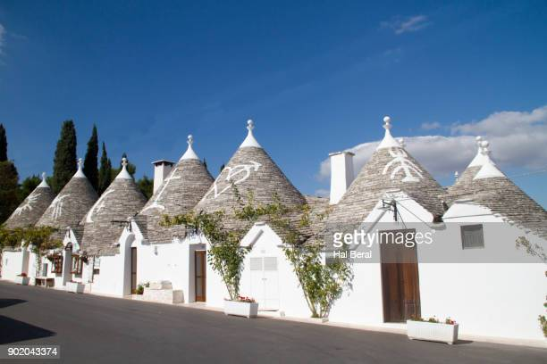 trulli houses with good luck symbols on the roofs - alberobello stock pictures, royalty-free photos & images