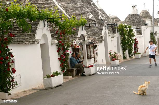 Trulli stand near Alberobello in the Puglia region southeast of Italy on May 8 2013 A trullo is a traditional Apulian dry stone hut with a conical...