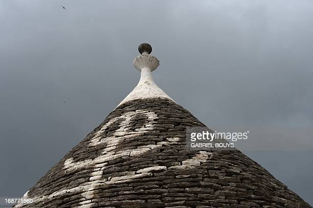 A trullo is seen in Alberobello in the Puglia region southEast of Italy on May 8 2013 A trullo is a traditional Apulian dry stone hut with a conical...