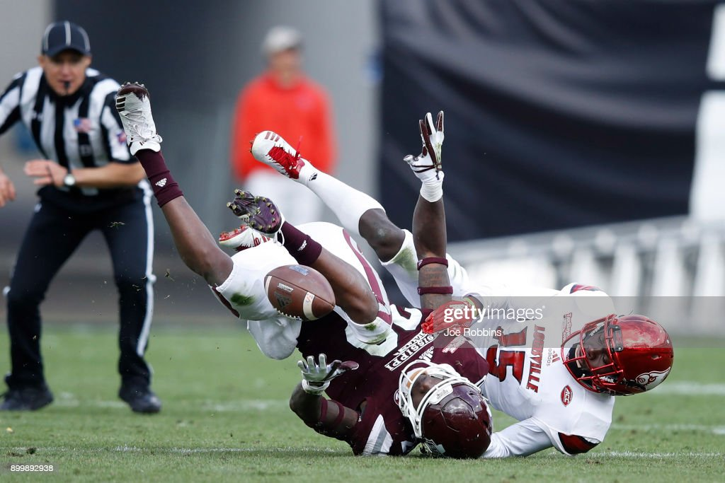 Trumaine Washington #15 of the Louisville Cardinals breaks up a pass intended for Reginald Todd #20 of the Mississippi State Bulldogs in the third quarter of the TaxSlayer Bowl at EverBank Field on December 30, 2017 in Jacksonville, Florida. The Bulldogs won 31-27.