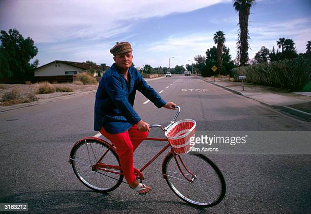 Truman Capote on his bicycle in Palm Springs California Author of several novels including 'Breakfast at Tiffany's' which was made into a film