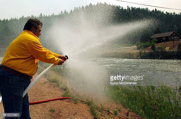 Trumbull resident Harry Glass sprays water of a hose that was pumping water from the South Platte River Glass was set up the pump and hoses to defend...