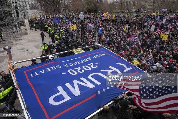 """Trump 2020"""" banner is carried as demonstrators swarm the U.S. Capitol building during a protest in Washington, D.C., U.S., on Wednesday, Jan. 6,..."""