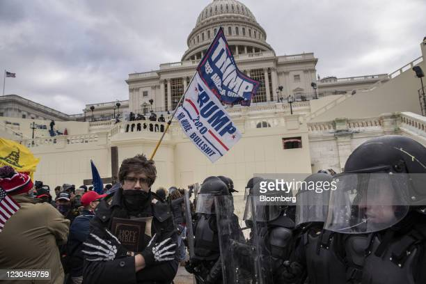 """""""Trump 2020"""" flags fly as demonstrators swarm the U.S. Capitol building during a protest in Washington, D.C., U.S., on Wednesday, Jan. 6, 2021. The..."""