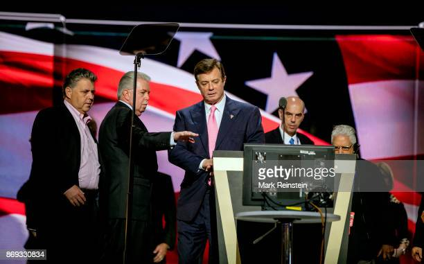 Trump campaign manager Paul Manafort talks with unidentified others on stage during the sound check on the final day of the Republican National...