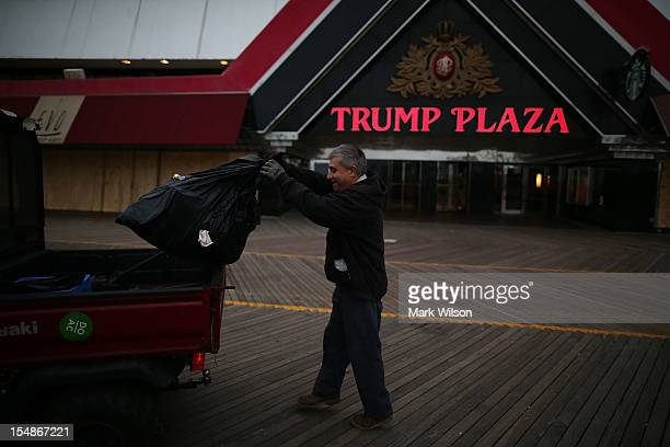 Trump employee Lou Ciabatoni empties a trash can on the boardwalk in front of the Trump Casino as Hurricane Sandy approaches on October 28 2012 in...