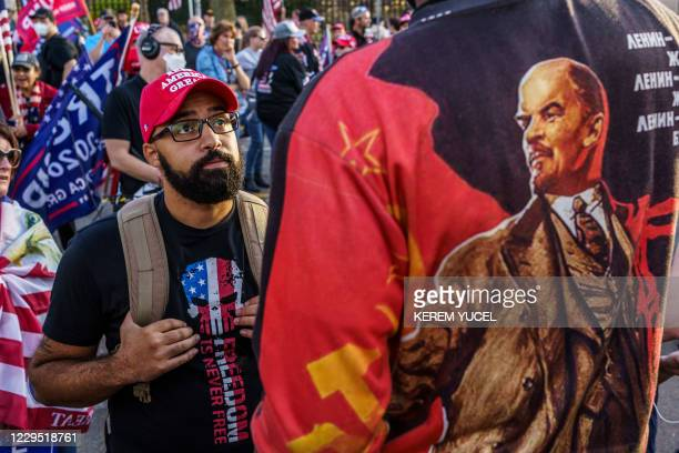 Trump supporter and a protester wearing a shirt with an image of Lenin exchange words in front of the residence of Minnesota Governor Tim Walz during...
