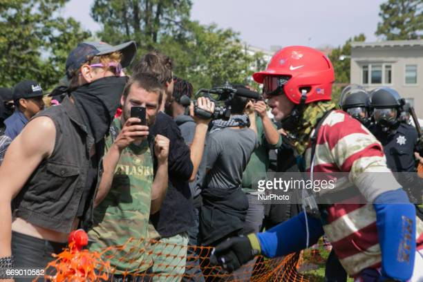 A Trump supporter and antifascist confront each other during a free speech rally at Martin Luther King Jr Civic Center Park in Berkeley California...