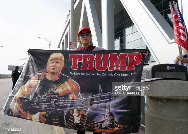 A Trump supporter holds a flag depicting the president as Rambo during a protest outside State Farm Arena where Fulton County Elections officials...
