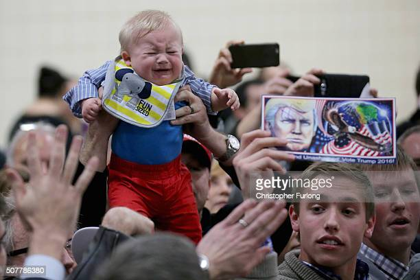 Trump supporter holds his child aloft for Republican presidential candidate Donald Trump to see, as other supporters clamour for autographs at a...