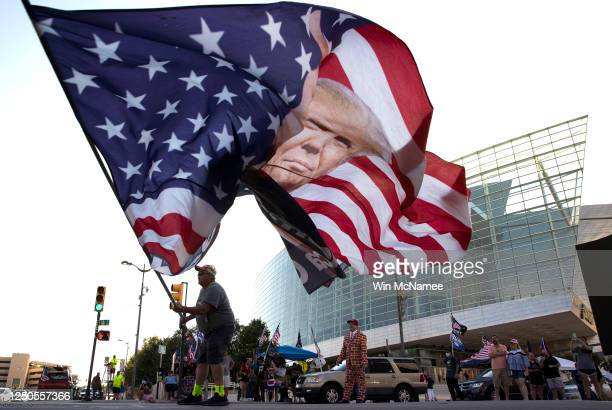 Trump supporter Randall Thom waves a giant Trump flag to passing cars outside the BOK Center June 18 2020 in Tulsa Oklahoma Trump is scheduled to...