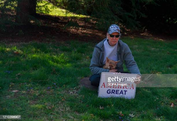 Trump supporter sits with a dog, while holding a Keep America Great placard during the demonstration. Protesters gather outside Indiana Governor Eric...