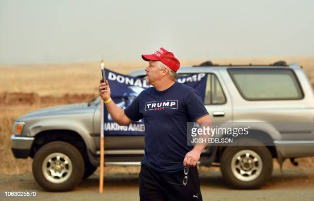A Trump supporter stands on the side of the road in anticipation of seeing the presidential motorcade in Chico California on November 16 2018...